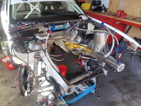 BMW E36 race car with an empty engine bay and front suspension
